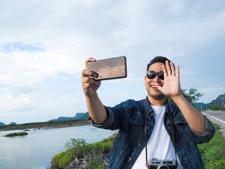 Asian tourist taking photo by his smart phone, lifestyle concept. Imagens