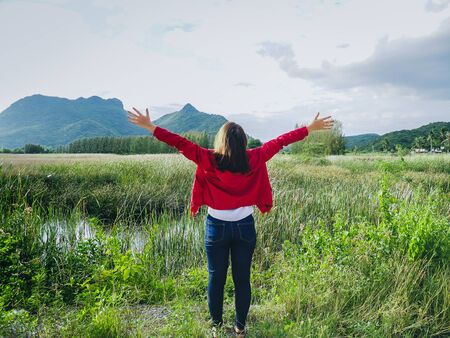 Back of woman wearing red jacket raising hand with nature view background, lifestyle concept. Reklamní fotografie