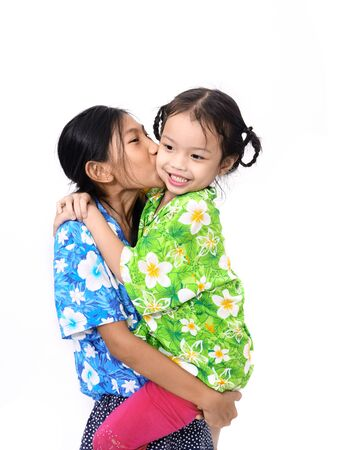 Happy Asian girl picking up her younger sister on white. Little girl kissing her sister.