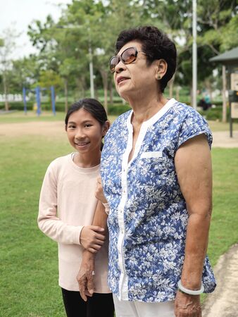 Asian senior woman walking in the park her grandchild, lifestyle concept.