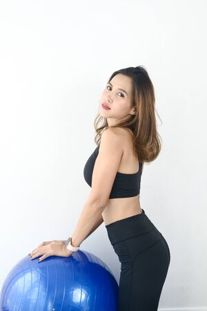 Asian sport woman sitting on blue ball pilates, lifestyle concept.