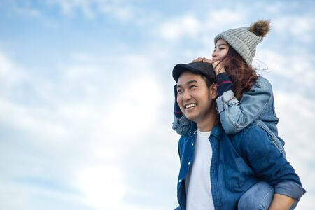 Piggy back Asian couple with blue sky and cloud, love concept.