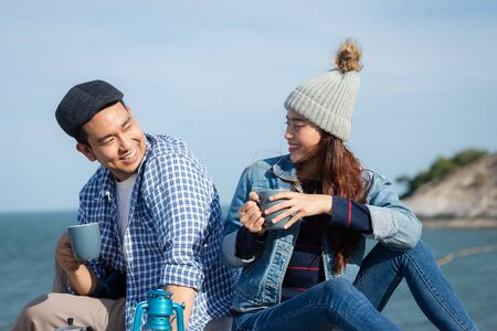 Happy Asian couple holding coffee cups on mountain peak together.