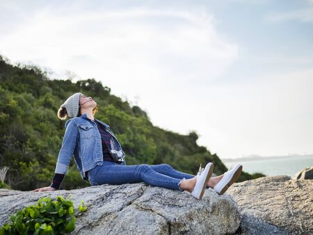 Asian woman relaxing on cliff facing to seaview, lifestyle concept.