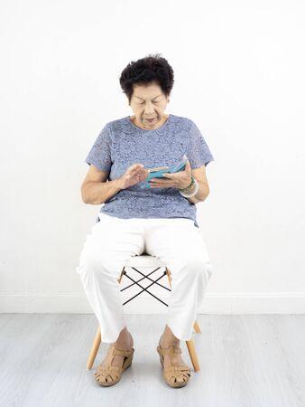 Asian senior woman  using smart phone at home. Stok Fotoğraf