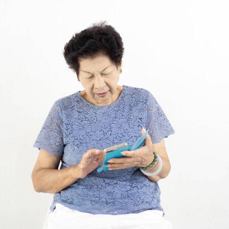 Asian senior woman  using smart phone at home. 免版税图像