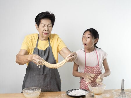 Asian senior woman and girl making dough for homemade pizza or bread, lifestyle concept. Stock Photo