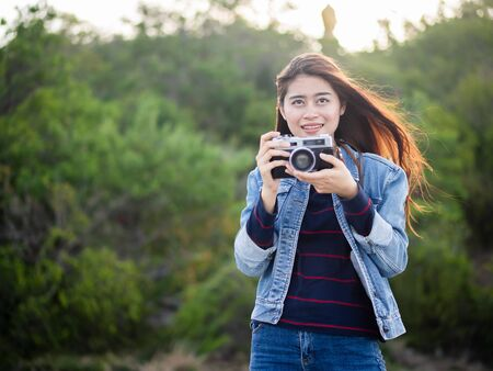 Happy Asian woman vintage camera with nature background, camping concept.