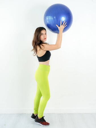 Asian sport woman holding blue ball pilates, lifestyle concept.