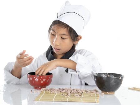 Asian girl learning how to making sushi on white background Stock Photo - 133827191