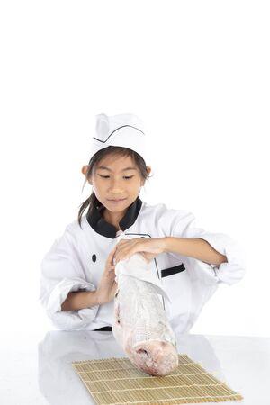 Surprising chef in uniform holding big freezing fish on white background. Imagens