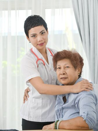 Do not give up! Asian doctor says to her patient old woman in office. Stok Fotoğraf