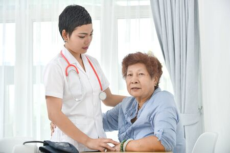 Do not give up! Asian doctor says to her patient old woman in office. Imagens