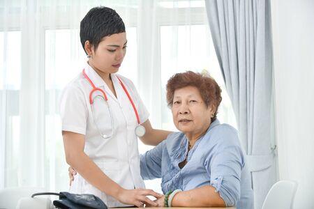 Nie poddawaj się! Azjatycki lekarz mówi do swojej pacjentki, starej kobiety w gabinecie. Zdjęcie Seryjne