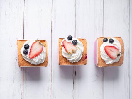 Cupcakes con glassa di crema di burro su fondo di legno bianco. Archivio Fotografico