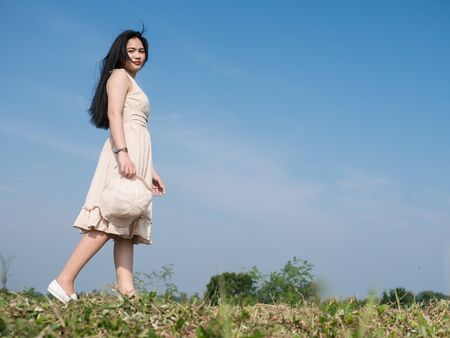 Asian woman wearing dress walking on green grass against blue sky, lifestyle concept.