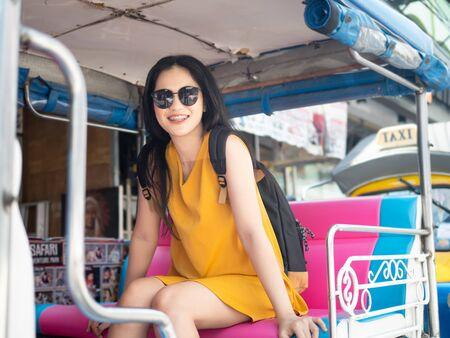 Happy Asian tourist sitting on Tuk Tuk taxi in Thailand.