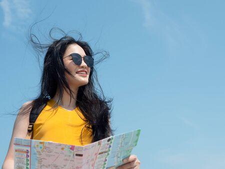 Asian tourist with map with blue sky, lifestyle concept. Banco de Imagens