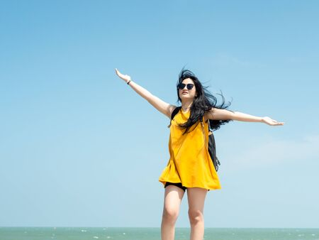 Asian woman with backpack raising hands on the pier.