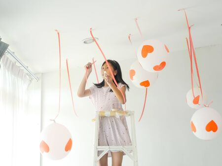 Blurry background Asian girl hanging balloon on ceiling, preparing for her party. Imagens