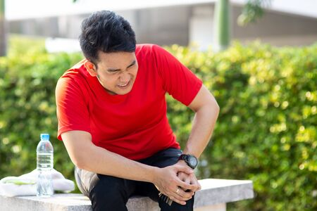 Asian sport man in red t-shirt hurts his leg with accident. Stockfoto