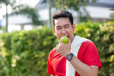 Happy Asian sport man with green apple in his hand outdoor. Фото со стока - 133666973