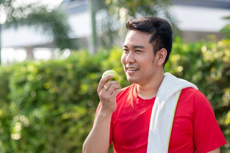 Happy Asian sport man with green apple in his hand outdoor. Фото со стока - 133666974