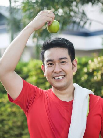 Happy Asian sport man with green apple in his hand outdoor. Фото со стока - 133667049