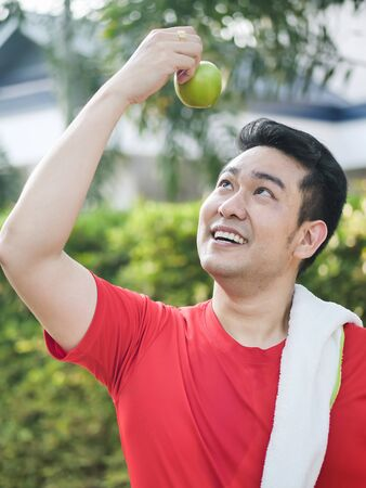 Happy Asian sport man with green apple in his hand outdoor. Фото со стока - 133667052
