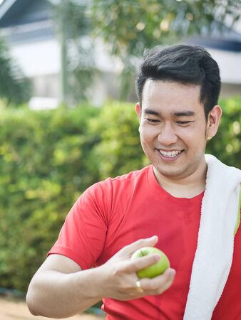 Happy Asian sport man with green apple in his hand outdoor. Фото со стока - 133667051