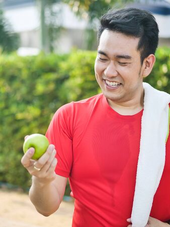 Happy Asian sport man with green apple in his hand outdoor.