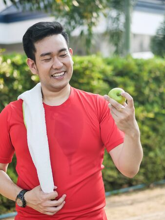 Happy Asian sport man with green apple in his hand outdoor. Фото со стока - 133667088