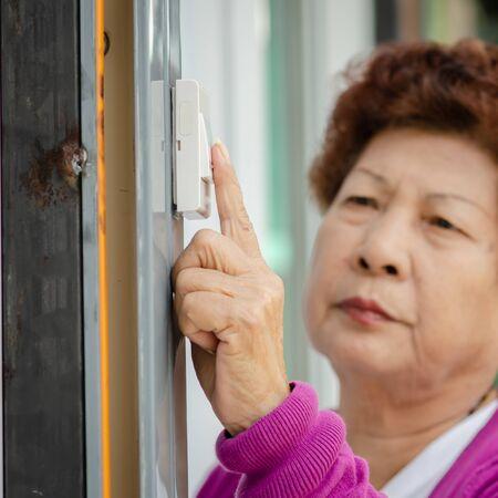 Asian senior woman clicking door bell, lifestyle concept.