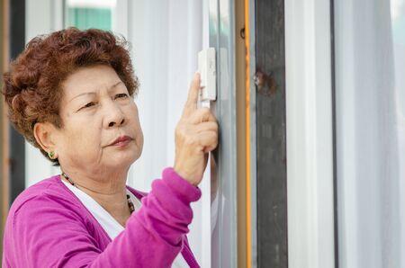 Femme senior asiatique en cliquant sur la sonnette de la porte, concept de style de vie. Banque d'images