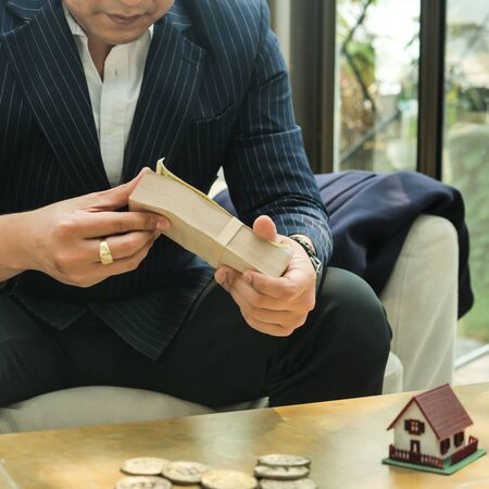 Rich businessman in real estate concept counting money in office. Banco de Imagens