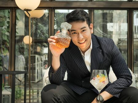 Handsome Asian businessman drinking fusion tea in cafe, lifestyle