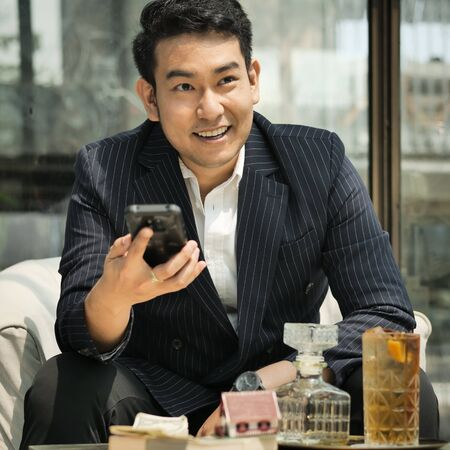 Rich businessman in real estate concept in cafe with smart phone.