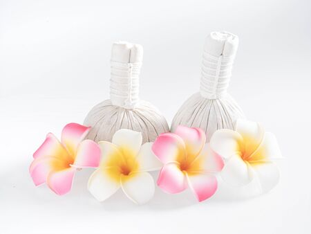 Herbal massage balls and yellow flowers isolated on white. Spa and massage concept. Stock Photo