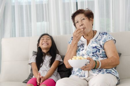 Asian senior woman eating popcorn with her grandchild while watching TV at home,