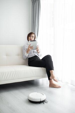 Intelligente Geschäftsfrau mit intelligentem Tablet und Reinigungsroboter, Lifestyle-Konzept. Standard-Bild