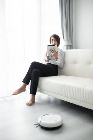 Smart businesswoman using smart tablet and cleaning robot, lifestyle concept. Banco de Imagens