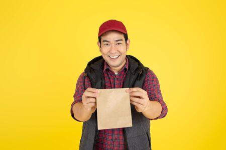 Divers contenants en papier pour plats à emporter. Le livreur porte sur fond jaune. Banque d'images