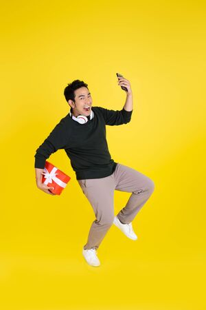 Happy Asian man holding gift box and smart phone, jumping on yellow background.