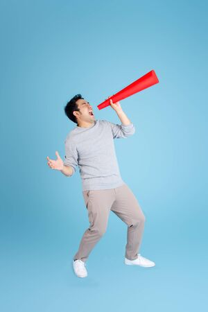 Asian man using red paper megaphone on blue background.