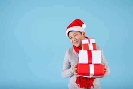 Asian preteen boy holding gift boxes on blue background, New Year and Christmas concept.