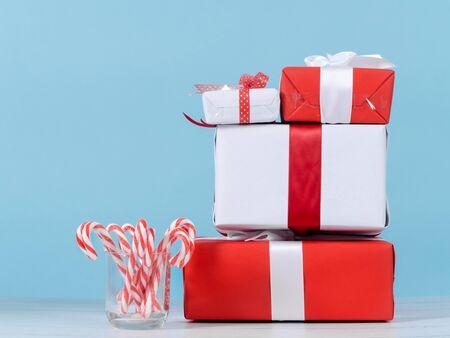 Scatole regalo rosse e bianche e bastoncini di caramelle natalizie su un tavolo di legno con parete blu.
