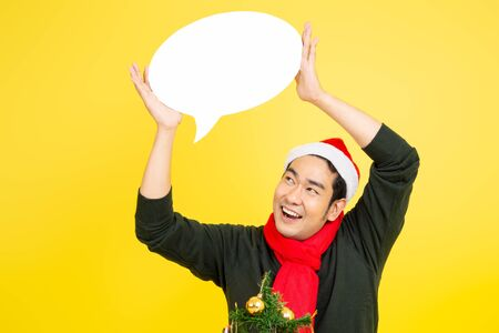 Asian man wearing sweater and Santa hat holding speech bubble on yellow background.