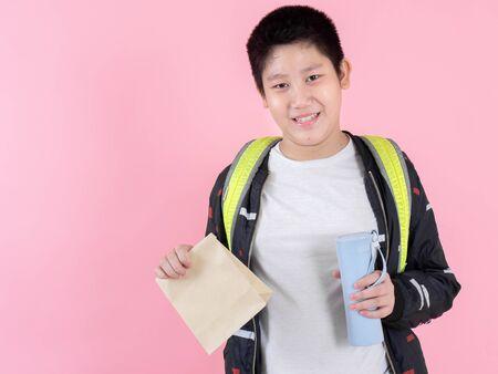 Garçon préadolescent asiatique montrant un sac à lunch et une bouteille de boisson, concept prêt à l'école. Banque d'images
