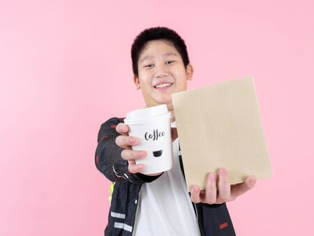 Heureux garçon préadolescent asiatique montrant un sac à lunch et un café à emporter sur fond rose.