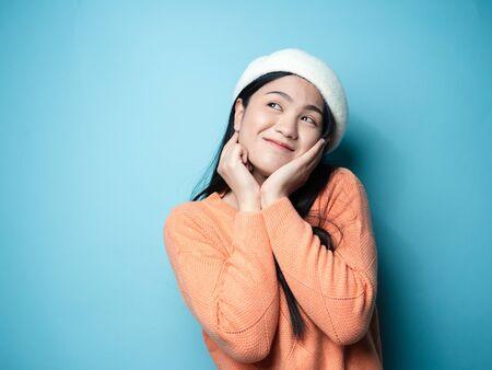 Asiatische Frau mit orangefarbenem Pullover auf blauem Hintergrund, Lifestyle-Konzept.
